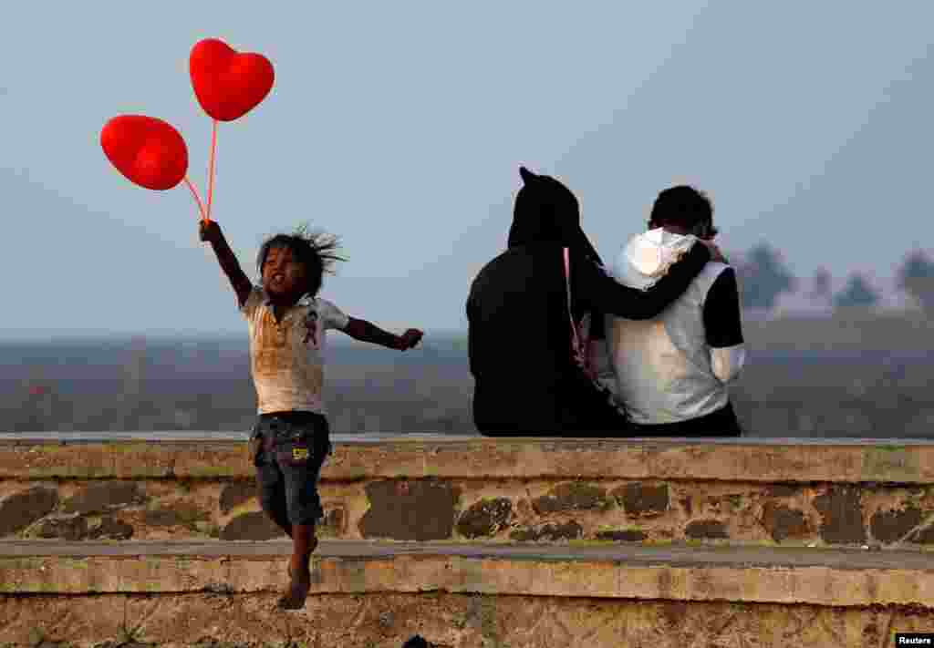 A child jumps from a promenade after attempting to sell heart-shaped balloons to a couple on Valentine's Day in Mumbai, India.