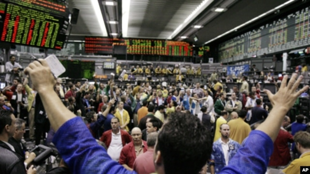 In this July 9, 2007 photo, traders in the S&P 500 Futures trading pit watch quote boards at the Chicago Mercantile Exchange in Chicago.
