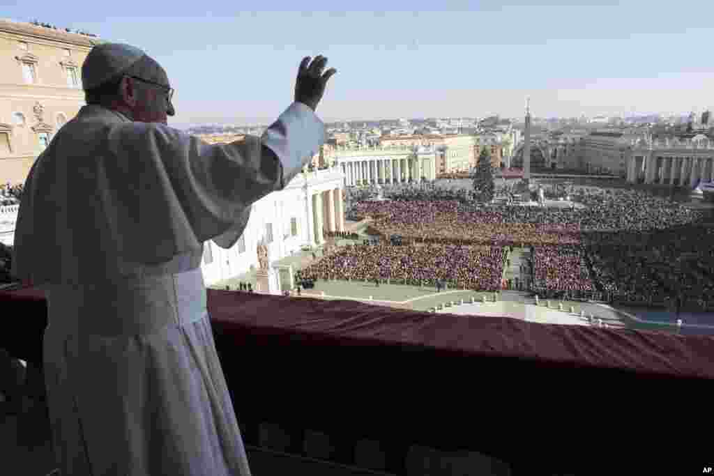 Pope Francis waves to faithful during the Urbi et Orbi (Latin for ' to the city and to the world') Christmas' day blessing from the main balcony of St. Peter's Basilica at the Vatican, Dec. 25, 2017.