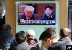 FILE - People watch a TV screen showing images of U.S. President Donald Trump, left, and North Korean leader Kim Jong Un at the Seoul Railway Station in Seoul, South Korea, Nov. 21, 2017.
