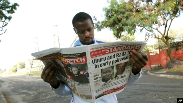 A Kenyan looks at a newspaper a day after the country's presidential election, at a roadside stall in Nairobi, Kenya,  March 5, 2013.