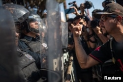 A demonstrator, part of a protest march against migrants, shouts towards a line of police in riot gear who were standing guard over a temporary shelter housing a caravan from Central America, in Tijuana, Mexico, Nov. 18, 2018.
