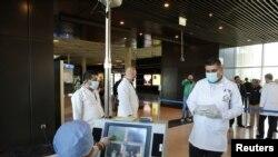 Anggota staf medis mengenakan alat pelindung diri bersiap memeriksa suhu para calon penumpang di Bandara Internasional Ratu Alia di Amman, Yordania, 4 Maret 2020. (Foto: Reuters)