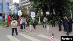 Para pengunjuk rasa memegang spanduk, potret almarhum pemimpin Tiongkok Mao Zedong, dan bendera Tiongkok di dekat barisan polisi yang berjaga di luar kantor pusat surat kabar Southern Weekly di Guangzhou, propinsi Guangdong. (8/1)