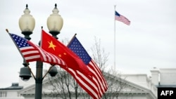 FILE - A lamp post is adorned with a Chinese national flag in between two U.S. flags in front of the White House in Washington, January 17, 2011.