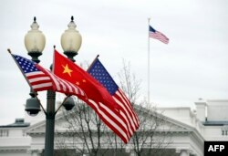 """FILE - A lamp post is adorned with a Chinese national flag in between two U.S. flags in front of the White House in Washington, D.C., Jan. 17, 2011, in honor of a visit to the U.S. by Chinese President Xi Jinping. Departing from established protocol, President-elect Donald Trump has not committed himself to continue the """"One China"""" policy followed by previous administrations."""