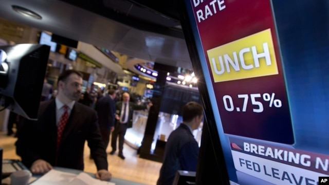 A television screen in a post on the floor of the New York Stock Exchange shows the decision of the Federal Reserve, January 30, 2013.
