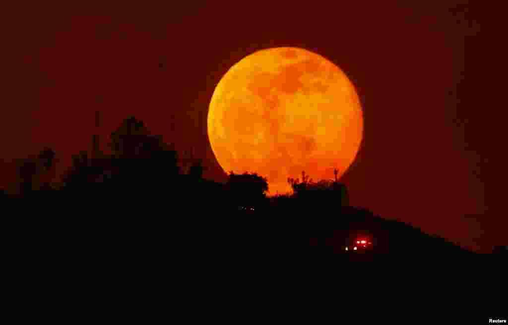 Chiec xe cứu thương chạy dọc theo một sườn đồi bị thiêu cháy ở San Marcos, California, trong khi trăng đang lên, ngày 14 tháng 5, 2014.