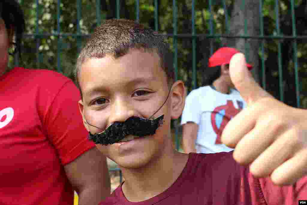 A young boy shows his support for Vice President Nicholas Maduro by wearing a mustache emulating that of Maduro.