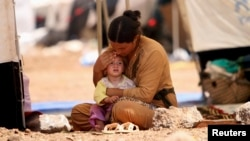 A refugee woman from the minority Yazidi sect, who fled the violence in the Iraqi town of Sinjar, sits with a child inside a tent at Nowruz refugee camp in Qamishli, northeastern Syria, Aug. 17, 2014.