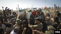 Para anggota pemberontak Libya mengangkat jenazah komandan militer, Abdel Fattah Younes dalam pemakaman di Benghazi (29/7).