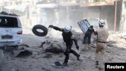 Para relawan mencari korban selamat pasca serangan udara Suriah terhadap posisi pemberontak di Aleppo (16/4).