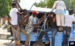 FILE - Vigilantes and local hunters armed with machetes and guns shout slogans as they gather outside the Emir's palace in Maiduguri, Nigeria, Sept. 4, 2014.