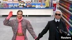 "Desainer Jerman Karl Lagerfeld (kanan) dan model Cara Delevingne dalam peragaan busana pekan mode Paris, yang diadakan di ""Pusat Perbelanjaan Chanel"" (4/3). (Reuters/Benoit Tessier)"