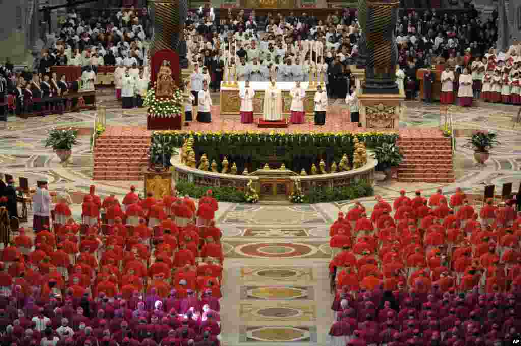 In this photo provided by the Vatican newspaper L'Osservatore Romano, Pope Francis, top center, leads a consistory inside the St. Peter's Basilica at the Vatican. Retired Pope Benedict XVI joined Pope Francis at a ceremony creating the cardinals who will elect their successor in an unprecedented blending of papacies past, present and future.