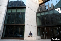 Seorang pria duduk di depan gedung Universitas Eropa Tengah, sebuah sekolah yang didirikan oleh pemodal AS George Soros, di Budapest, Hongaria, 9 April 2018. (Foto: Reuters)