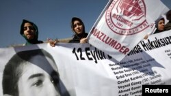 Human rights activists hold a banner with a portrait of Erdal Eren, a leftist executed during the military rule after the coup in 1980, as they demonstrate in front of a courthouse in Ankara, April 4, 2012.