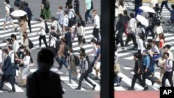 A man sits near a window as people wearing face masks walk along a pedestrian crossing at Shibuya district Sept. 30, 2021, in Tokyo.