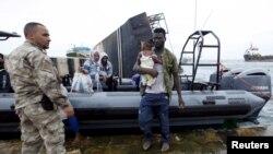 Un migrant portant un enfant, débarque d'un bateau de l'armée sous la surveillance d'un militaire de la marine libyenne à Tripoli, Libye, 7 septembre 2015