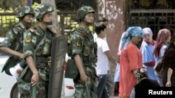 Pasukan keamanan China melakukan patroli di kota Urumqi, Xinjiang (29/6).