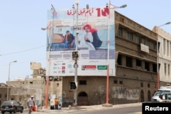 "A man walks past a billboard displaying an advertisement for the local movie ""10 Days Before the Wedding"" in Aden, Yemen, Sept. 1, 2018."