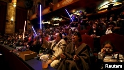 "Moviegoers cheer and wave lightsabers before the first showing of the movie ""Star Wars: The Force Awakens"" at the TCL Chinese Theatre in Hollywood, California, Dec. 17, 2015."