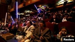 "FILE - Moviegoers cheer and wave lightsabers at ""Star Wars: The Force Awakens"" at the TCL Chinese Theatre in Hollywood, California, Dec. 17, 2015."