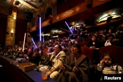 """FILE - Movie-goers cheer and wave lightsabers before the first showing of the movie """"Star Wars: The Force Awakens"""" at the TCL Chinese Theatre in Hollywood, California, Dec. 17, 2015."""