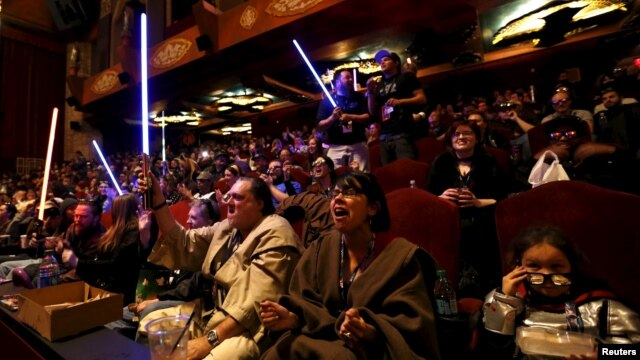 """FILE - Moviegoers cheer and wave lightsabers at """"Star Wars: The Force Awakens"""" at the TCL Chinese Theatre in Hollywood, California, Dec. 17, 2015."""