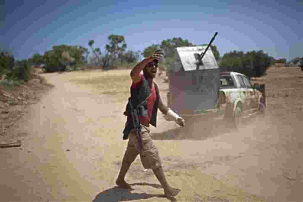 یکی از مبارزان مخالف قذافی به همرزمان خود فرمان می دهد. ۲۶ مه ۲۰۱۱