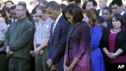 President Barack Obama, first lady Michelle Obama, and members of the White House staff observe a moment of silence to mark the 11th anniversary of the September 11, 2001 terrorist attacks on the South Lawn of the White House.