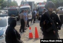 Polisi berjaga saat proses memasukkan jenazah yang disimpan di kontainer ke dalam peti jenazah di mobil ambulance (Foto:VOA/Petrus Riski).