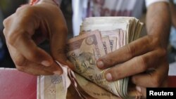 A grocery shop owner counts rupees notes in the western Indian city of Ahmedabad, May 23, 2012.