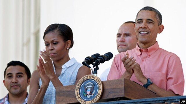 President Barack Obama and first lady Michelle Obama applaud during a Fourth of July celebration on the South Lawn of the White House, July 4, 2013.