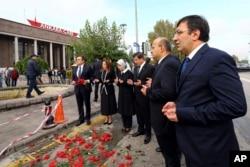 Turkish Prime Minister Ahmet Davutoglu, third right, his wife Sare Davutoglu, third left, his deputies Yalcin Akdogan, second right, and Cevdet Yilmaz, right, pray at the site of an explosion in Ankara, Turkey, Oct. 13, 2015.