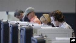 Para pemilih memasukkan suara pada pemilu pendahuluan Partai Republik di TPS Frederick, Maryland.