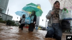 Women wade through a flooded street in Jakarta, Indonesia, January 17, 2013.