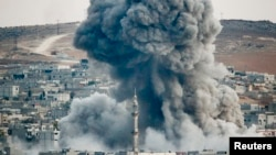 Smoke rises over Syrian town of Kobani after an airstrike, as seen from the Mursitpinar border crossing on the Turkish-Syrian border in the southeastern town of Suruc, Sanliurfa province, Oct. 18, 2014.