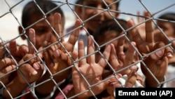 """Anak-anak pengungsi Suriah menunjukkan tanda """"V"""" yang berarti victory atau kemenangan di kamp pengungsi Suruc di Turki (foto: dok)."""