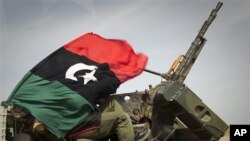A Libyan rebel is covered up in the rebels flag next to his weapon as he moves on the road bewteen Al-Egila and Ras Lanuf, eastern Libya, Sunday, March 27, 2011