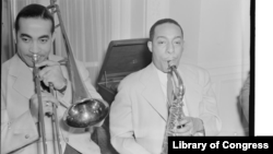 Jazz musicians Lawrence Brown and Johnny Hodges of the Duke Ellington Orchestra are shown playing together at the Turkish ambassador's residence. William P. Gottlieb/Library of Congress