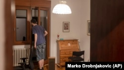 In this photo taken on Friday, July 2, 2021, Nemanja Dragic, 36,opens his door as noise from a local bar fills his apartment in Belgrade, Serbia. Serbia's capital is alive with nightlife again after over a year of pandemic restrictions with bars and other nightlife places opening again. (AP Photo/Marko Drobnjakovic)