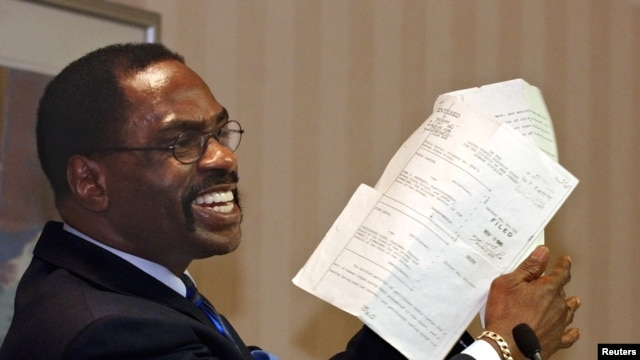 "FILE - In this Jan. 29, 2004, file photo, former boxer, Rubin ""Hurricane"" Carter, holds up the document that freed him from prison, during a news conference held in Sacramento, California."