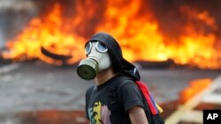 An anti-government protester stands in front of burning barricade on a highway in Caracas, Venezuela, April 24, 2017.