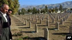 Men stand at a graveyard where the dead of 1988 gas attack on Halabja, Iraq, by Saddam Hussein's regime were laid to rest, Dec. 7, 2006. (AP Photo/Yahya Ahmed)