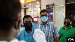 ဘဂၤလားေဒ့ရွ္ႏိုင္ငံ Dhaka ၿမိဳ႕က ဘဏ္ထဲ မ၀င္ခင္ အ၀င္ေပါက္မွာ ကိုယ္အပူခ်ိန္တိုင္းေနတဲ့ ၀န္ထမ္း တဦး။ (ဧၿပီ ၀၂၊ ၂၀၂၀)