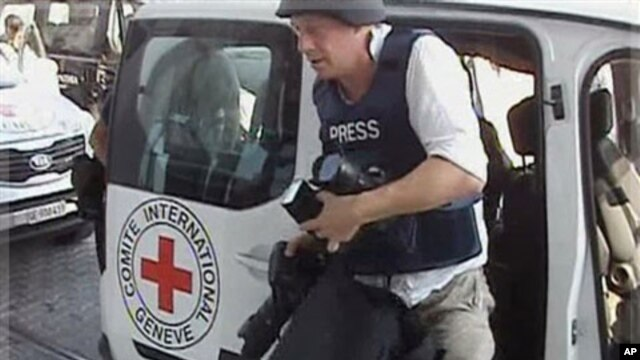 A journalist arrives at the Corinthia hotel after being evacuated from the Rixos Hotel in Tripoli in this image taken from TV Wednesday Aug. 24, 2011.