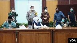 Khofifah Indar Parawansa (tengah) dan Tri Rismaharini (kanan) saat memberi keterangan pers terkait penetapan PSBB di Surabaya, Sidoarjo dan Gresik (foto: VOA/Petrus Riski).
