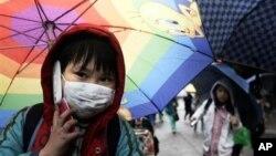 Seorang siswa SDI di Seoul, Korea Selatan, berbicara di ponselnya sambil memegang payung. (Foto: Dok)