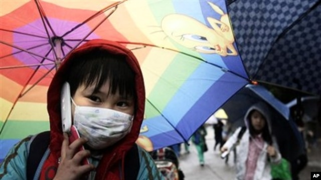A South Korean student holding an umbrella talks on his mobile phone as he goes to his home amid fears that the rain may contain radioactive materials from the crippled nuclear reactors in Japan at Midong elementary school in Seoul, April 7, 2011